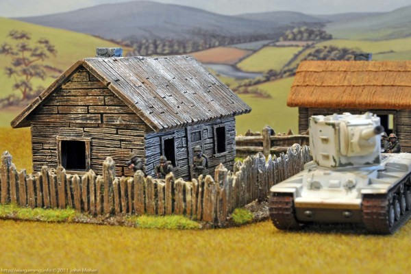 The KV-2 rumbles past the Area 9 long Farm House with Wooden Roof